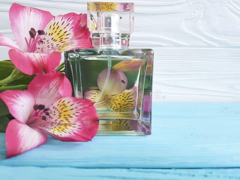 Bottiglia di alstroemeria del fiore del profumo bello su un fondo di legno immagini stock libere da diritti