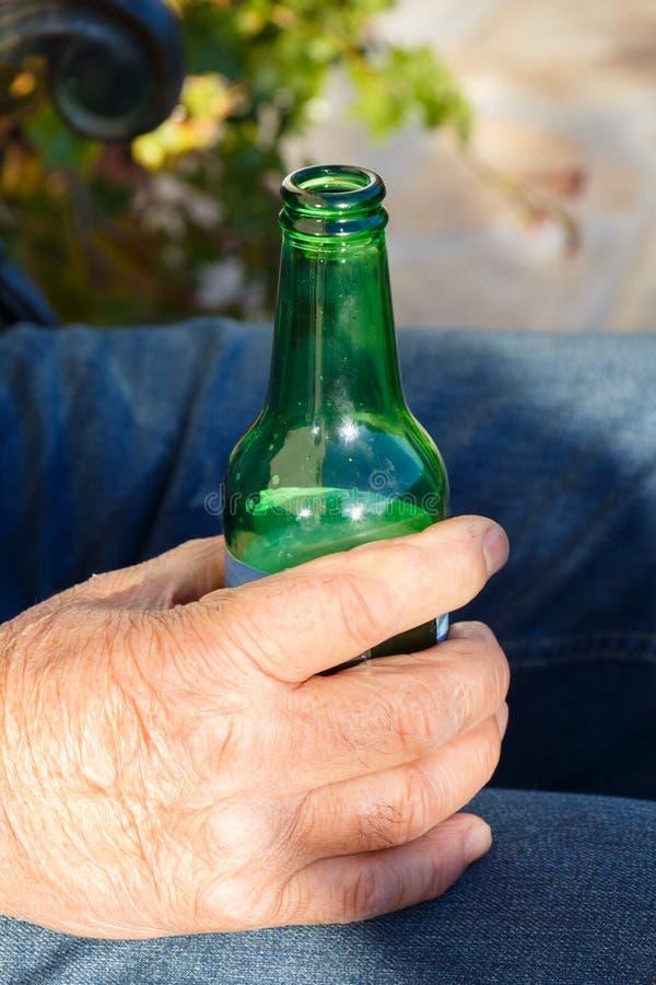 Bottiglia di birra aperta nella mano di un uomo fotografia stock libera da diritti