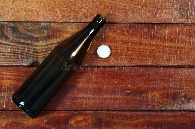 Bottiglia di birra aperta vuota su fondo di legno rustico fotografie stock libere da diritti