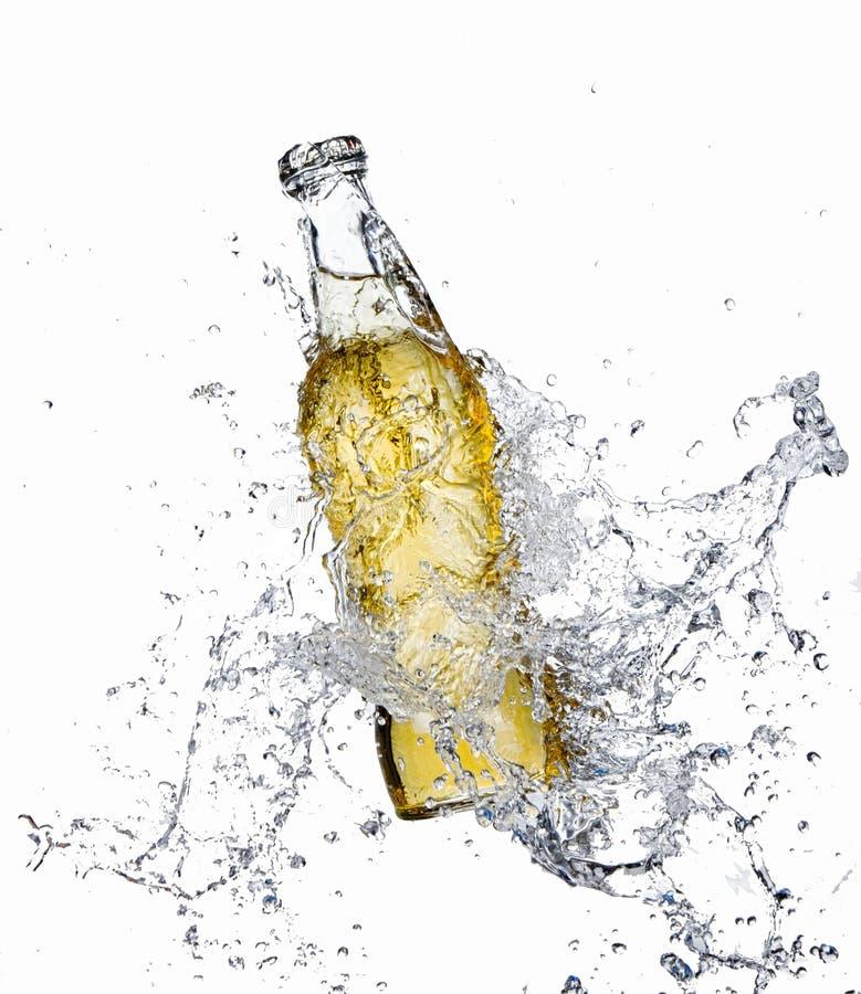 Bottiglia di birra con la spruzzata dell'acqua immagine stock libera da diritti