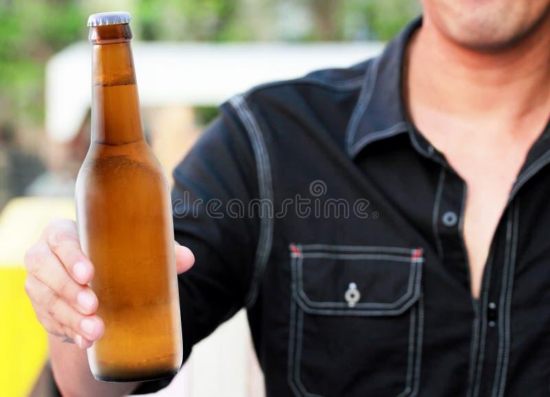Bottiglia di birra a disposizione fotografia stock