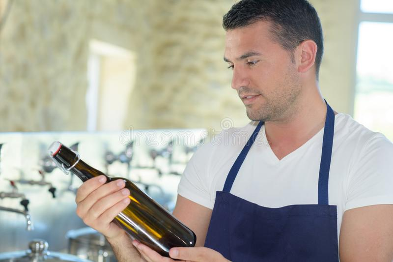 Bottiglia di birra felice della tenuta del fabbricante di birra del ritratto immagini stock libere da diritti