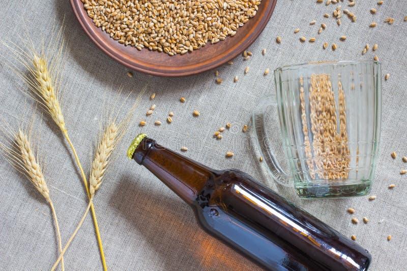 Bottiglia di birra, grano, tazza vuota su tela di sacco immagini stock