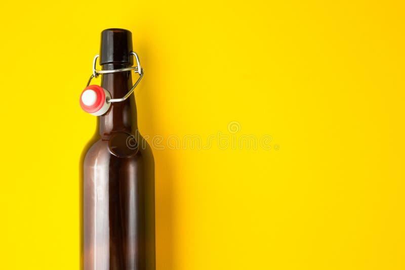 Bottiglia di birra marrone d'annata isolata su un fondo giallo Spazio per testo immagini stock libere da diritti