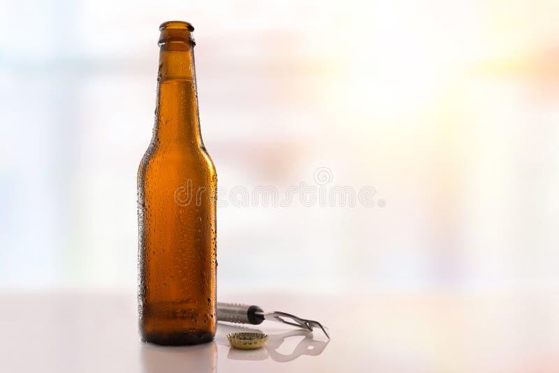 Bottiglia di birra riempita ed aperta sul fondo di vetro della luce della tavola immagine stock libera da diritti