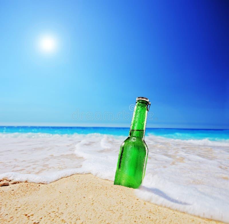 Bottiglia di birra su una spiaggia sabbiosa con il chiari cielo ed onda fotografie stock libere da diritti