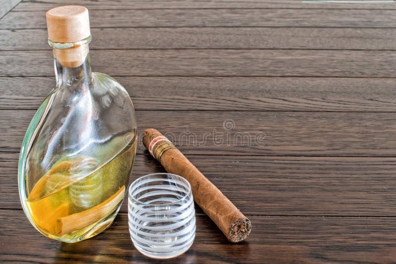 Bottiglia di brandy con il sigaro ed il vetro fotografia stock