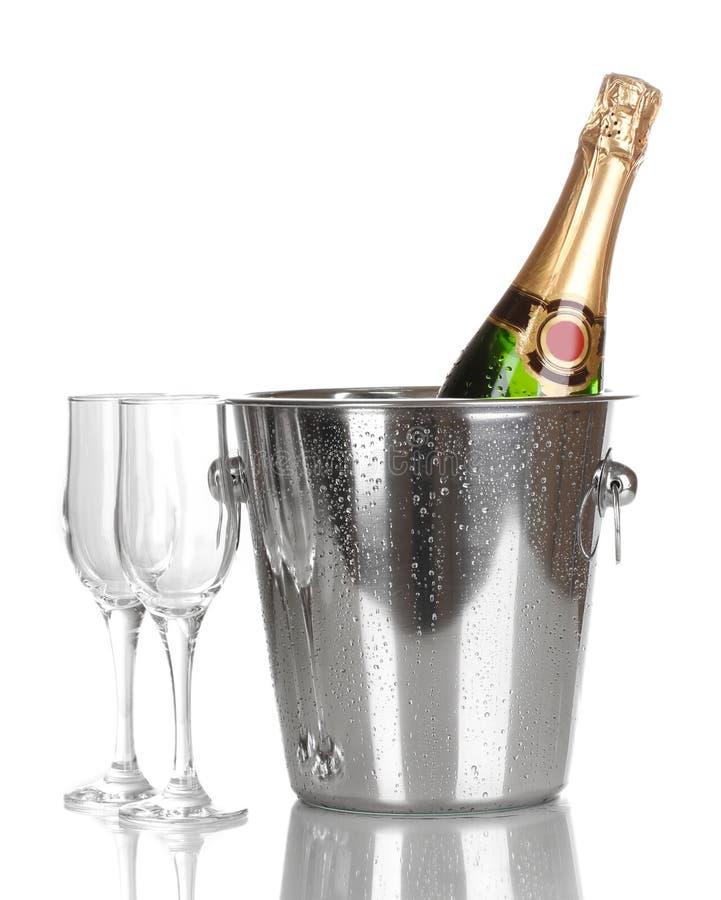 Bottiglia di champagne in benna e calici fotografia stock