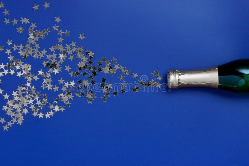 Bottiglia di Champagne con la decorazione di natale dalle stelle dei coriandoli fotografie stock libere da diritti