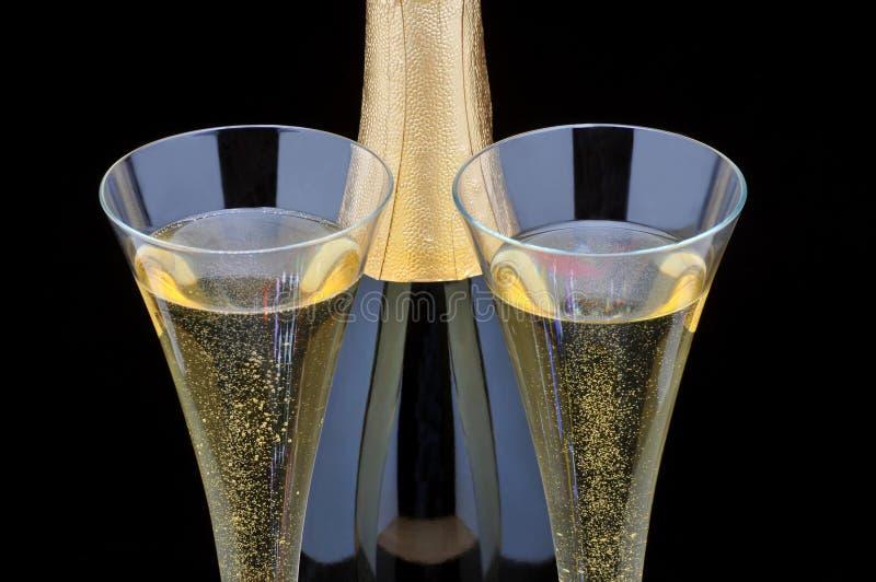 Bottiglia di Champagne e due scanalature immagini stock libere da diritti