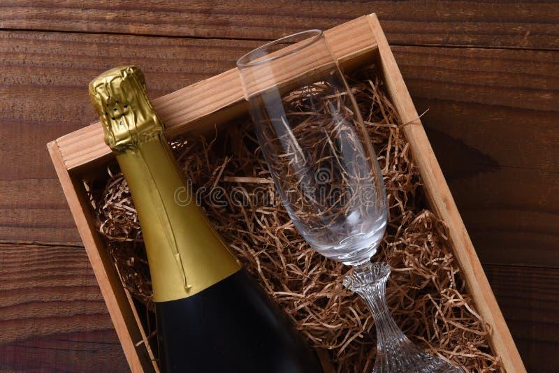Bottiglia di Champagne in un contenitore di regalo di legno con una flauto a cristallo fotografia stock libera da diritti