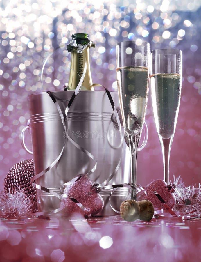 Bottiglia di champagne in un secchio con ghiaccio e bicchieri di champagne su fondo scuro Tema celebrazione con champagne fotografia stock libera da diritti