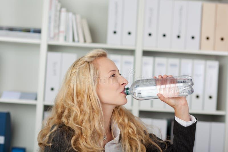 Bottiglia di Drinking Water From della donna di affari immagini stock