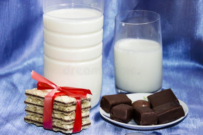 bottiglia di latte con fondo ed il biscotto blu fotografia stock libera da diritti