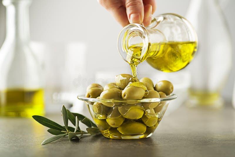 Bottiglia di olio d'oliva che versa per lanciare vicino su immagine stock