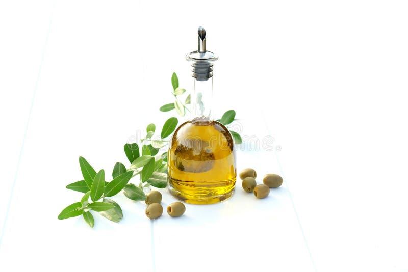 Bottiglia di olio d'oliva con le olive ed e un ramo di ulivo fotografia stock libera da diritti