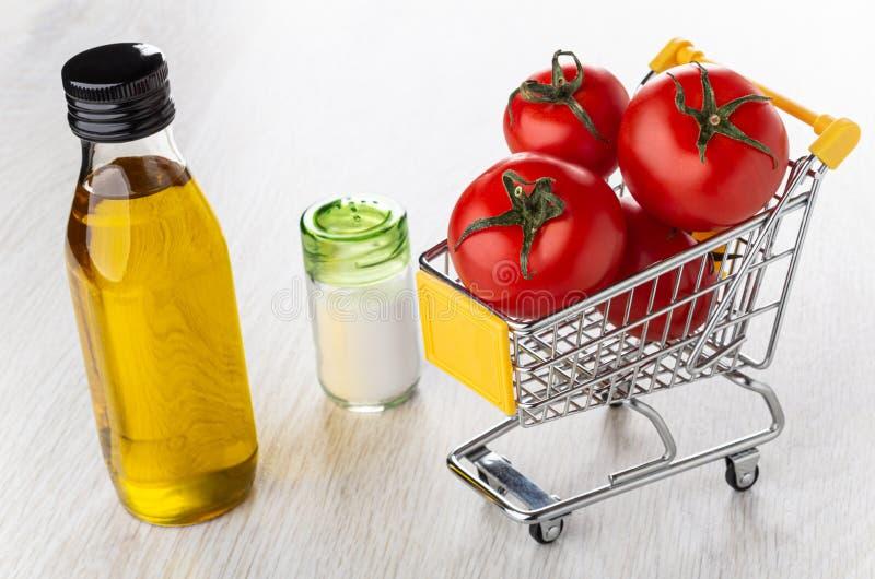 Bottiglia di olio vegetale, sale, carrello con i pomodori rossi sulla tavola di legno fotografia stock libera da diritti