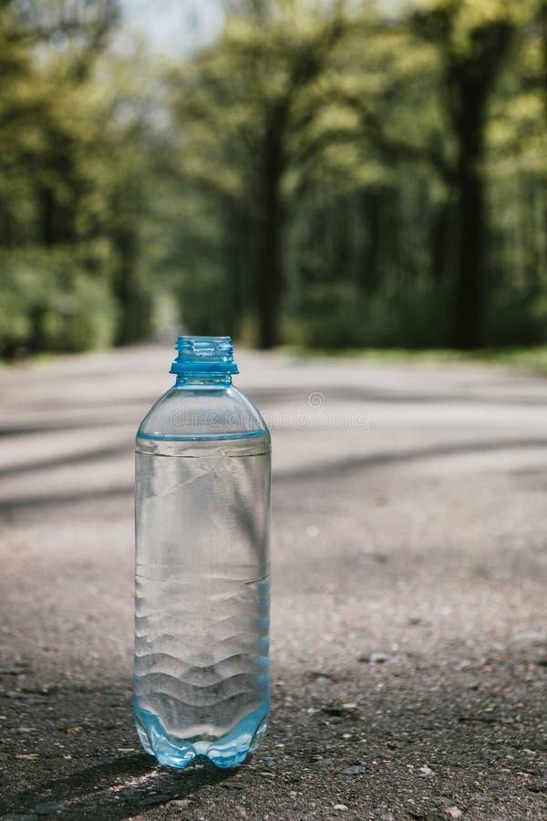 Bottiglia di plastica di acqua potabile pulita sulla strada, fonte di vita immagini stock