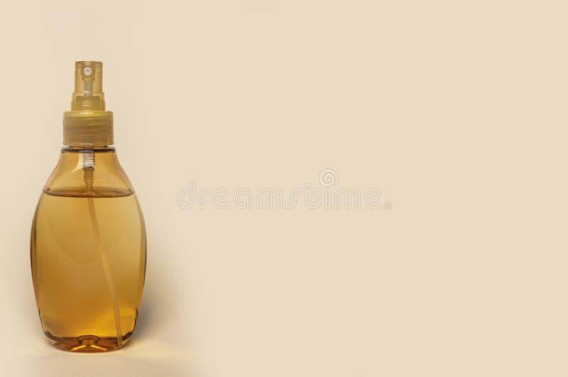 Bottiglia di plastica con spruzzo e l'olio giallo di massaggio fotografia stock libera da diritti