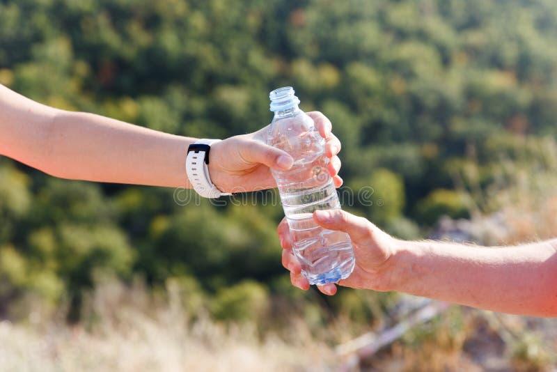 Bottiglia di plastica della tenuta maschio e femminile della mano di acqua all'aperto fotografia stock libera da diritti