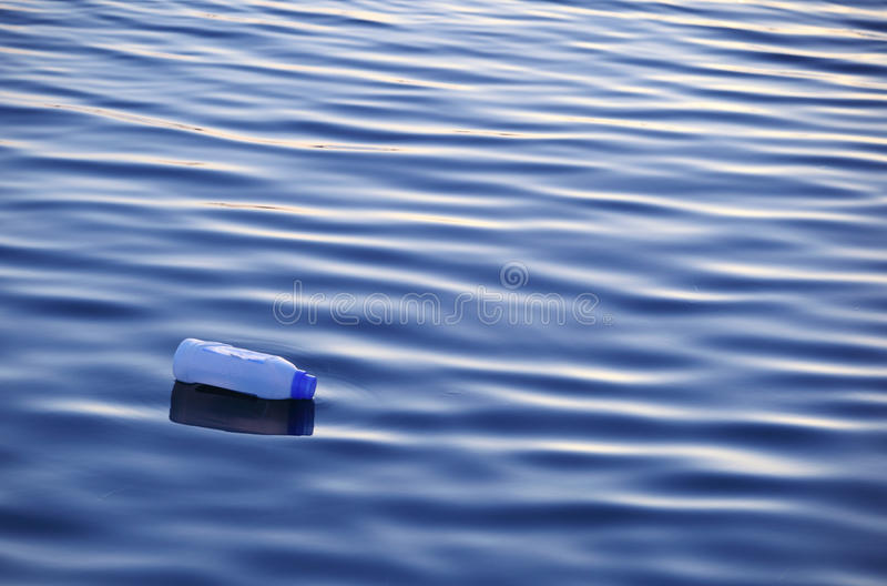 Bottiglia di plastica su acqua fotografia stock