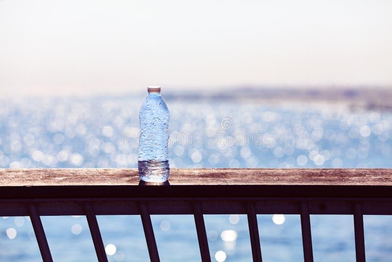 Bottiglia di plastica vuota su una balaustra del pilastro al tramonto fotografie stock libere da diritti