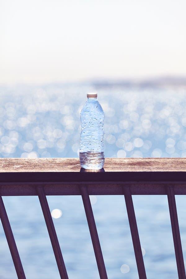Bottiglia di plastica vuota su una balaustra del pilastro al tramonto immagini stock