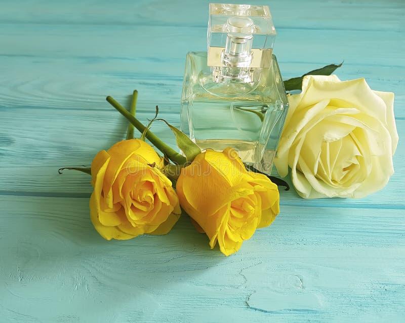 Bottiglia di profumo con le rose gialle su un fondo di legno fotografia stock libera da diritti