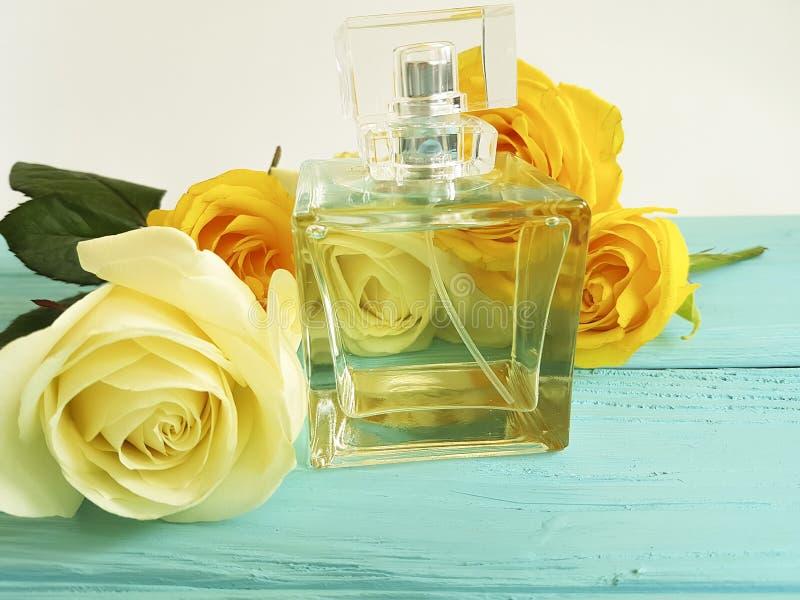 Bottiglia di profumo con le rose gialle su un di legno immagine stock libera da diritti