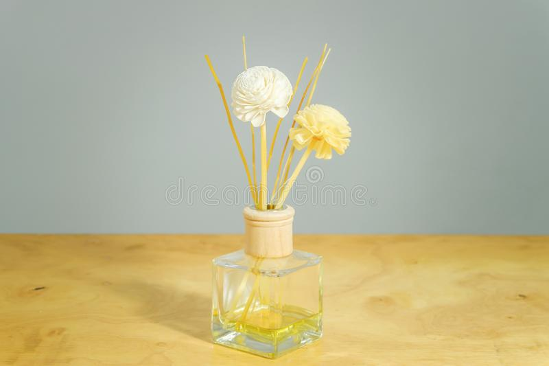 Bottiglia di profumo del fiore sul fondo della tavola fotografia stock