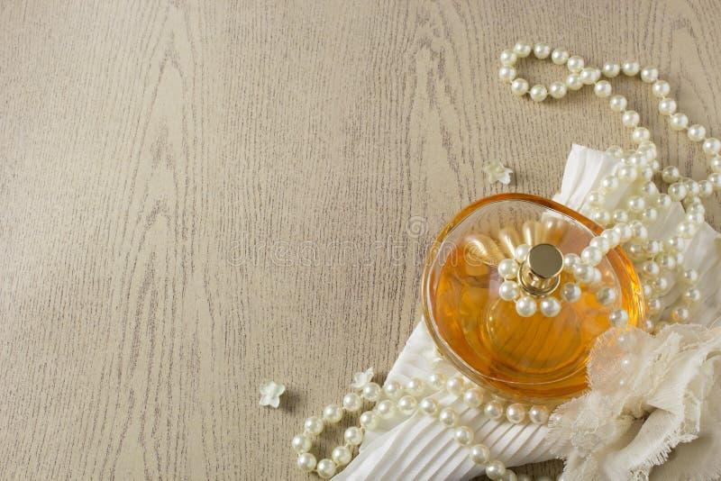 Bottiglia di profumo di eleganza con le perle bianche fotografie stock