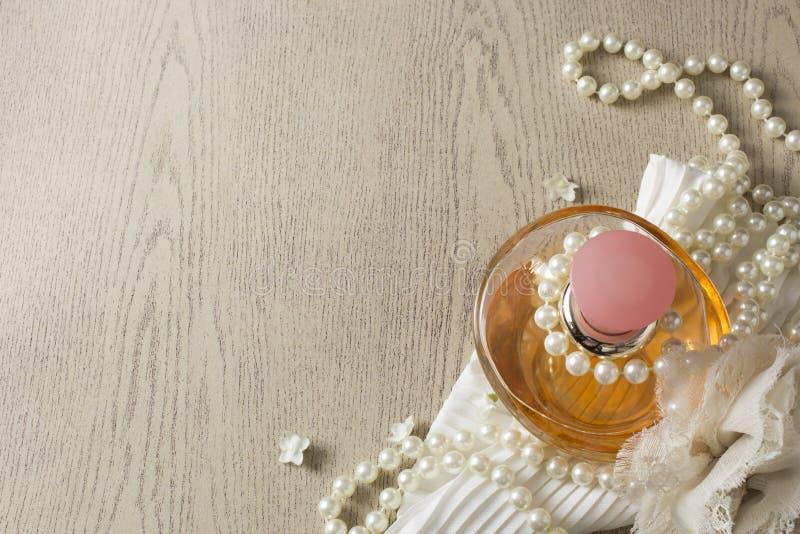 Bottiglia di profumo di eleganza con le perle bianche immagini stock