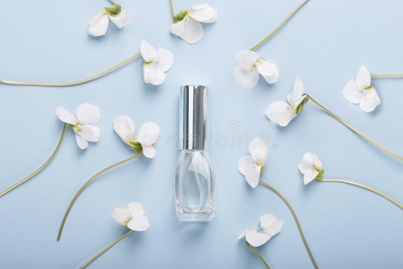 Bottiglia di profumo sui fiori della pansé immagini stock libere da diritti