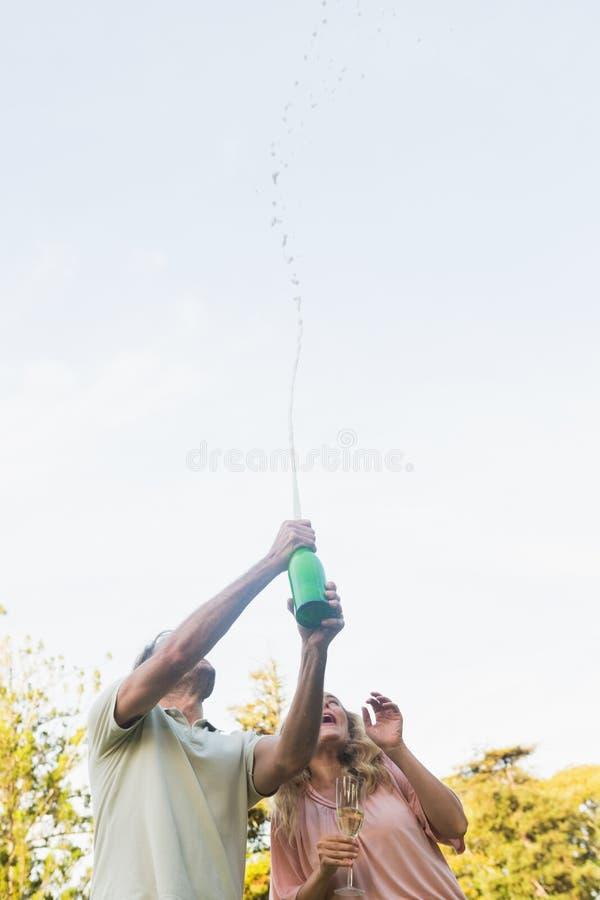 Bottiglia di spruzzatura dell'uomo bello di champagne con il partner biondo fotografia stock