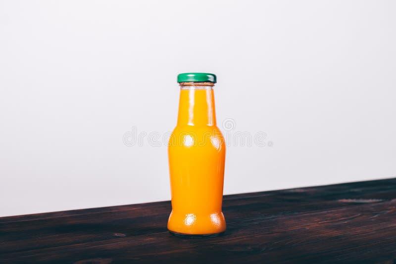 Bottiglia di succo d'arancia con il cappuccio verde immagine stock