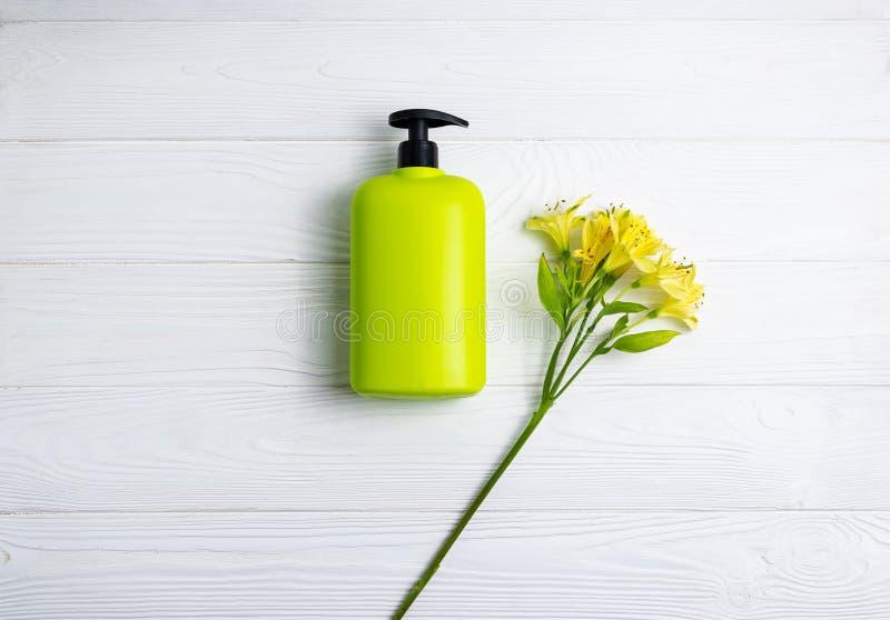 Bottiglia di verde del gel della doccia o dello sciampo con i fiori su fondo di legno bianco immagini stock