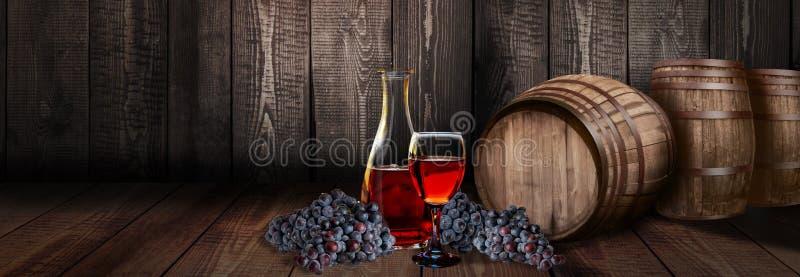 Bottiglia di vetro del vino rosso con il barilotto sul legno della vigna fotografia stock