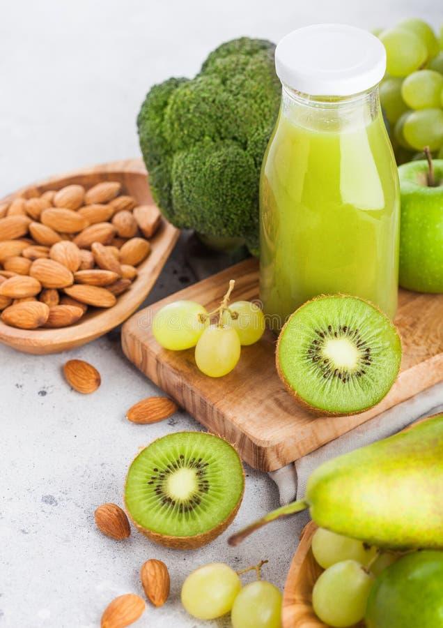 Bottiglia di vetro della frutta tonificata verde organica e delle verdure del succo fresco del frullato sul fondo di pietra della immagini stock