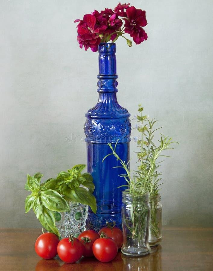 Bottiglia di vetro, ortaggi e fiori blu immagini stock