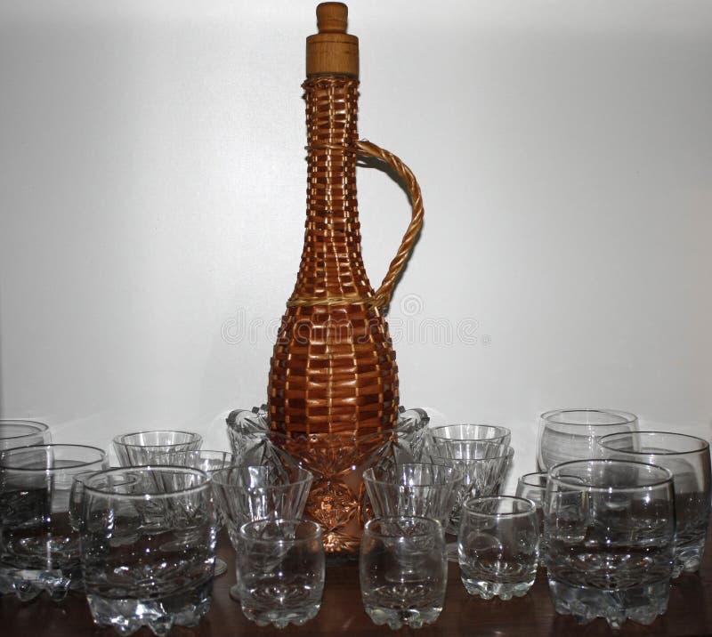 bottiglia di vimini della paglia con un collo lungo, circondato dai vetri e dai vetri per vino su un fondo bianco in una credenza immagini stock