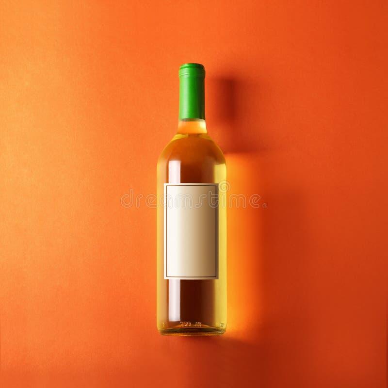 Bottiglia di vino bianco, fondo arancio fotografia stock
