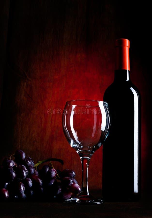 Bottiglia di vino con i vetri e l'uva fotografie stock