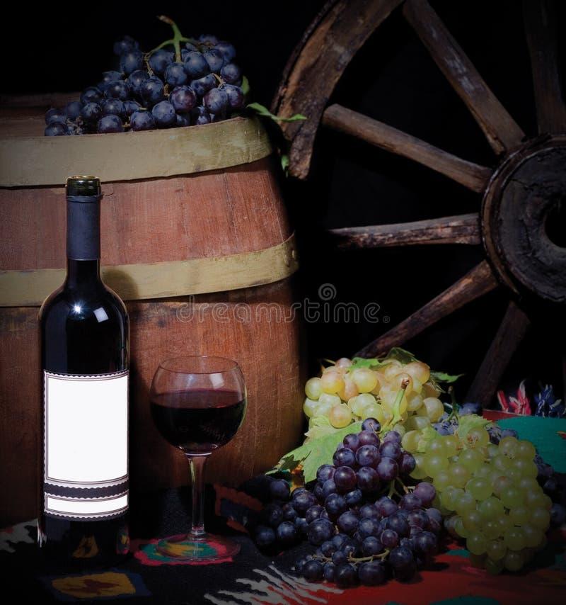 Bottiglia di vino con l'uva ed il barilotto immagine stock libera da diritti
