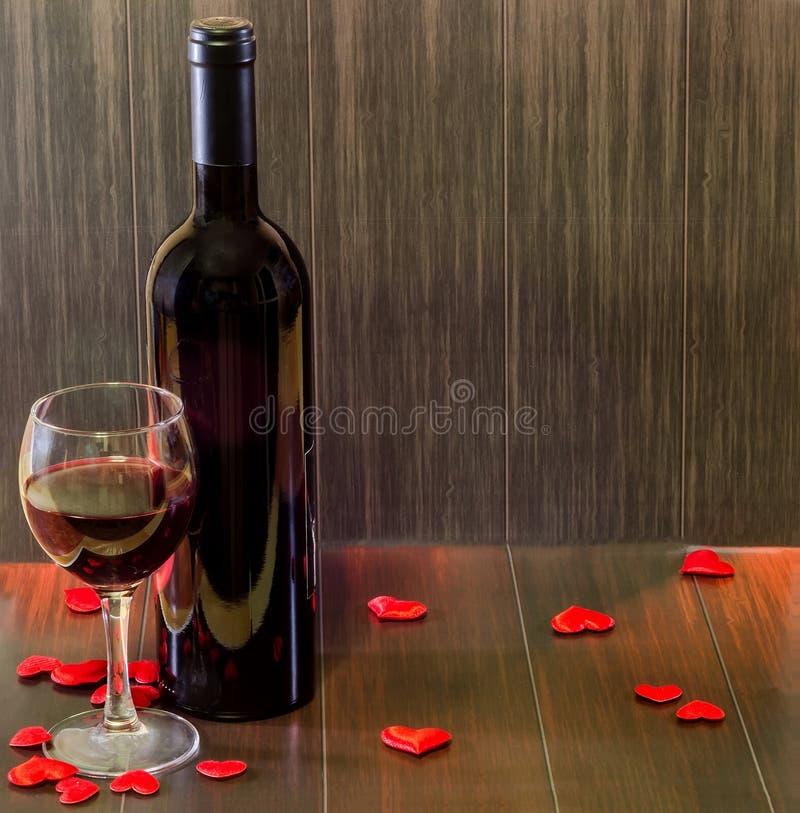 Bottiglia di vino con vetro trasparente con vino rosso, cuori rossi del tessuto, fondo di legno di struttura, fine su immagini stock libere da diritti