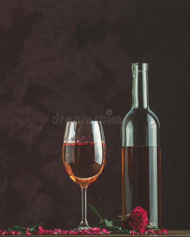 Bottiglia di vino di rosa e di vetro servita con vino di rosa e petali di rosa, rosa rosa su fondo scuro fotografie stock libere da diritti
