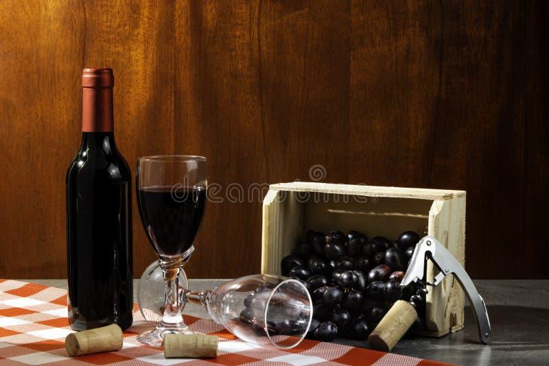 Bottiglia di vino rosso in cantina per avere un sapore Fondo di legno rosso con la scatola di legno con l'uva Tradizione del vino fotografia stock libera da diritti