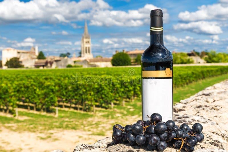 Bottiglia di vino rosso contro lo sfondo delle vigne di Saint Emilion, Bordeaux, Francia immagini stock libere da diritti