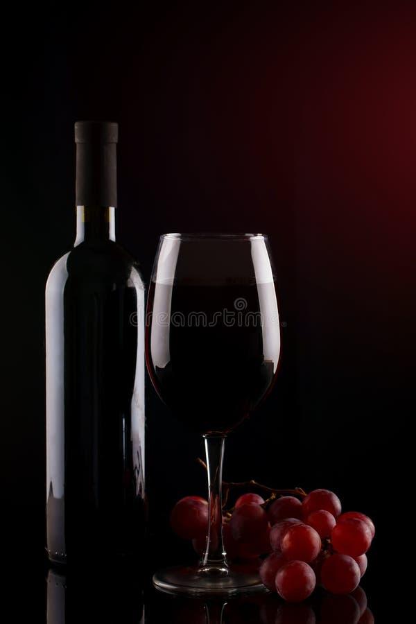 Bottiglia di vino rosso, di un vetro di vino rosso e dell'uva su un fondo scuro immagini stock libere da diritti