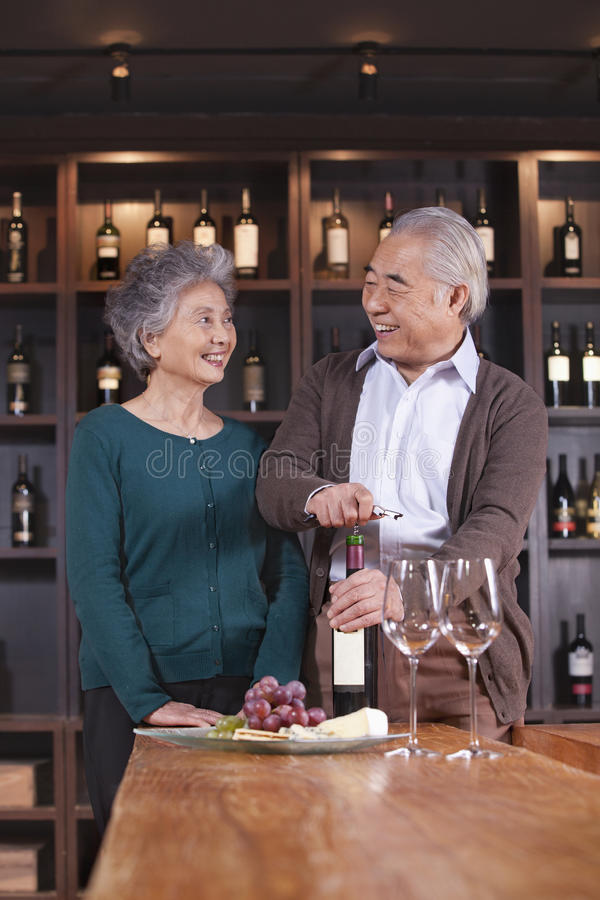 Bottiglia di vino senior di apertura delle coppie fotografia stock