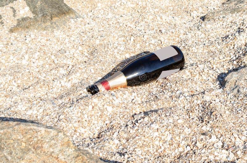 Bottiglia di vino di vetro vuota che si trova sulla sabbia di una spiaggia del mare fotografia stock libera da diritti